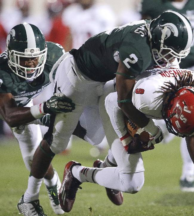 Jacksonville State wide receiver Anthony Johnson (9) is brought down by Michigan State cornerback Darian Hicks (2) and safety Mark Meyers (29) in the second half of an NCAA college football game in East Lansing, Mich., Friday, Aug. 29, 2014