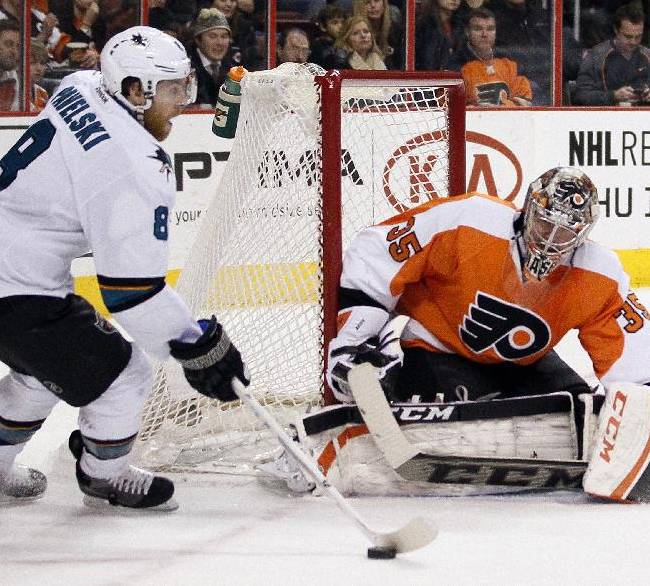 San Jose Sharks' Joe Pavelski, left, maneuvers the puck near the net as Philadelphia Flyers' Steve Mason defends during the first period of an NHL hockey game on Thursday, Feb. 27, 2014, in Philadelphia