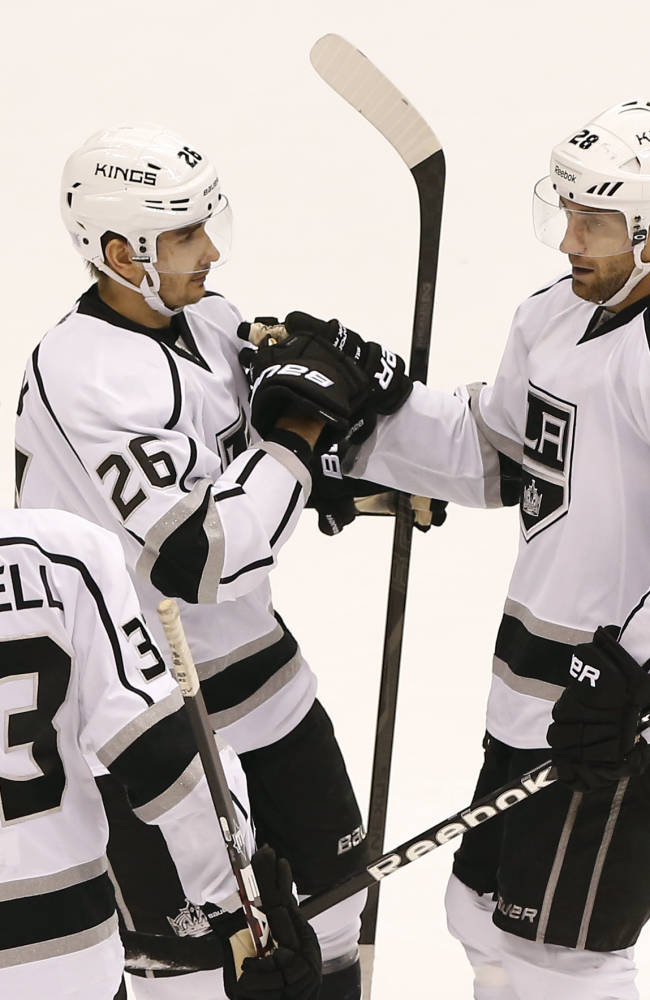 Los Angeles Kings' Jake Stoll (28) celebrate his goal with teammates Slava Voynov (26), of Russia, and Willie Mitchell (33) during the third period of an NHL hockey game against the Phoenix Coyotes, Tuesday, Oct. 29, 2013, in Glendale, Ariz. The Coyotes won 3-1