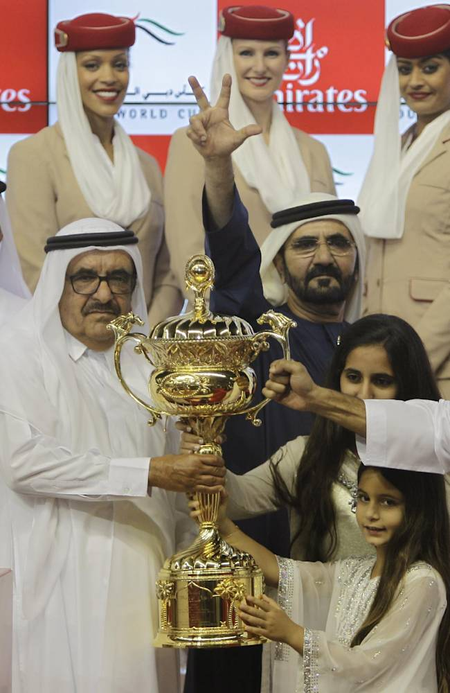 Sheikh Mohammed bin Rashid Al Maktoum, UAE prime minister and ruler of Dubai, center, gestures after African Story from Great Britain and UAE Godolphin Club won the Dubai World Cup at Meydan racecourse in Dubai, United Arab Emirates, Saturday, March 29, 2014