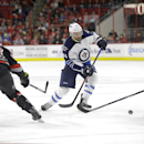 Winnipeg Jets' Zach Bogosian (44) skates between Carolina Hurricanes' Ron Hainsey (65) and John-Michael Liles (26) during the first period of an NHL hockey game in Raleigh, N.C., Thursday, Nov. 13, 2014 The Associated Press