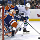 Vancouver Canucks' Shawn Matthias (27) is stopped by Edmonton Oilers goalie Ben Scrivens (30) as Justin Schultz (19) defends during first period NHL hockey action in Edmonton, Alberta, on Saturday April 12, 2014 The Associated Press