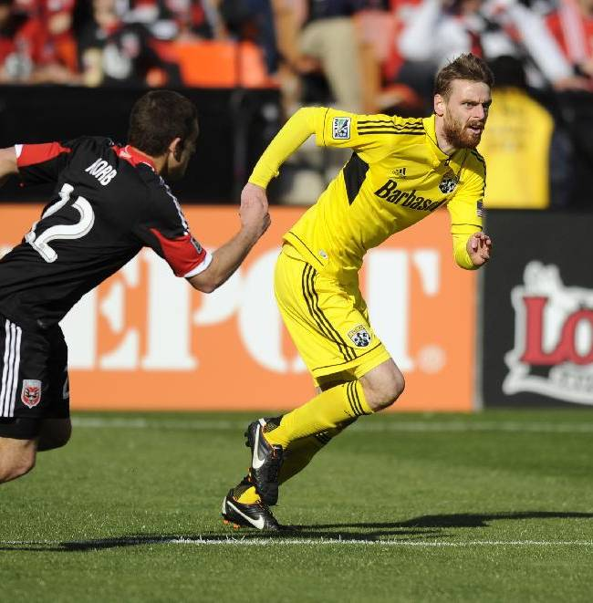 In this March 23, 2013, photo, Columbus Crew midfielder Eddie Gaven, right, chases the ball against D.C. United defender Chris Korb during an MLS soccer game in Washington. The Crew has announced that Gaven is retiring after 11 seasons in the league. The 27-year-old concludes a career that includes 278 appearances, 51 goals and 37 assists in MLS regular-season competition