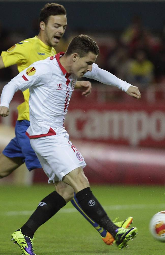 Sevilla's Kevin Gameiro kicks to score his side's first goal next to Estoril's Yohan Tavares during a Group H Europa League  soccer match between Sevilla and Estoril at the Ramon Sanchez Pizjuan stadium in Sevilla, Spain, Thursday, Nov. 28, 2013