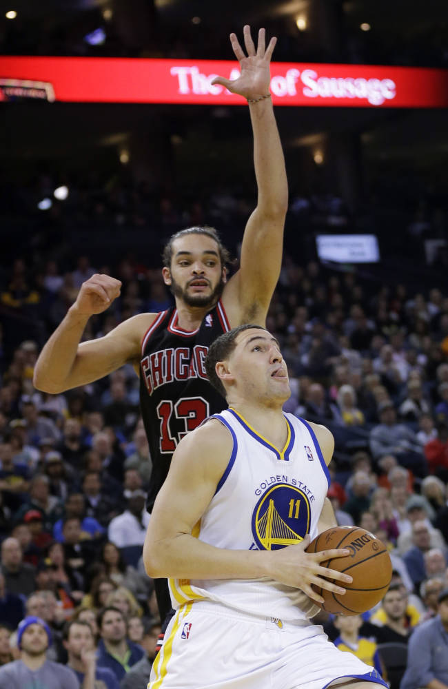 Golden State Warriors' Klay Thompson (11) drives past Chicago Bulls' Joakim Noah (13) during the second half of an NBA basketball game on Thursday, Feb. 6, 2014, in Oakland, Calif. Golden State won 102-87
