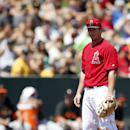 Los Angeles Angels' David Freese stands next to a ground ball hit by San Francisco Giants' Hunter Pence after Freese is unable to field the ground ball during the first inning of a spring training baseball game Monday, March 24, 2014, in Tempe, Ariz The A