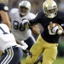 Notre Dame running back Theo Riddick, right, runs past BYU defensive back Joe Sampson during the second half of an NCAA college football game in South Bend, Ind., Saturday, Oct. 20, 2012. Notre Dame defeated BYU 17-14. (AP Photo/Michael Conroy)