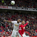 Manchester United's Chris Smalling, right, fights for the ball against Swansea City's Ashley Williams during their English Premier League soccer match at Old Trafford Stadium, Manchester, England, Saturday Aug. 16, 2014