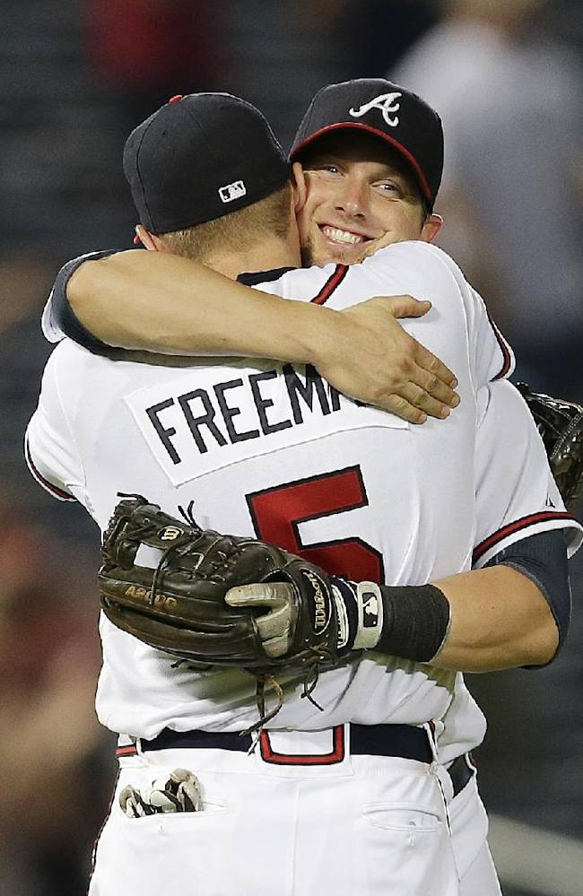 Atlanta Braves' Chris Johnson embraces teammate Freddie Freeman after defeating New York Mets 5-3 in a baseball game on Wednesday, June 19, 2013, in Atlanta