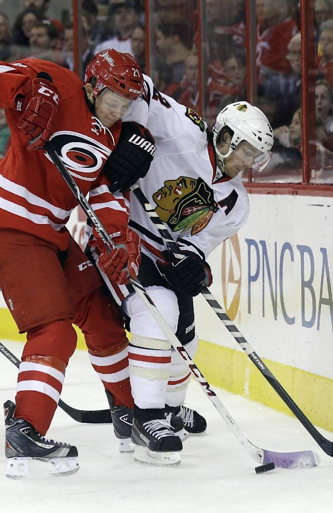 Chicago Blackhawks' Duncan Keith, right and Carolina Hurricanes' Drayson Bowman struggle for possession during the second period of an NHL hockey game in Raleigh, N.C., Tuesday, Oct. 15, 2013