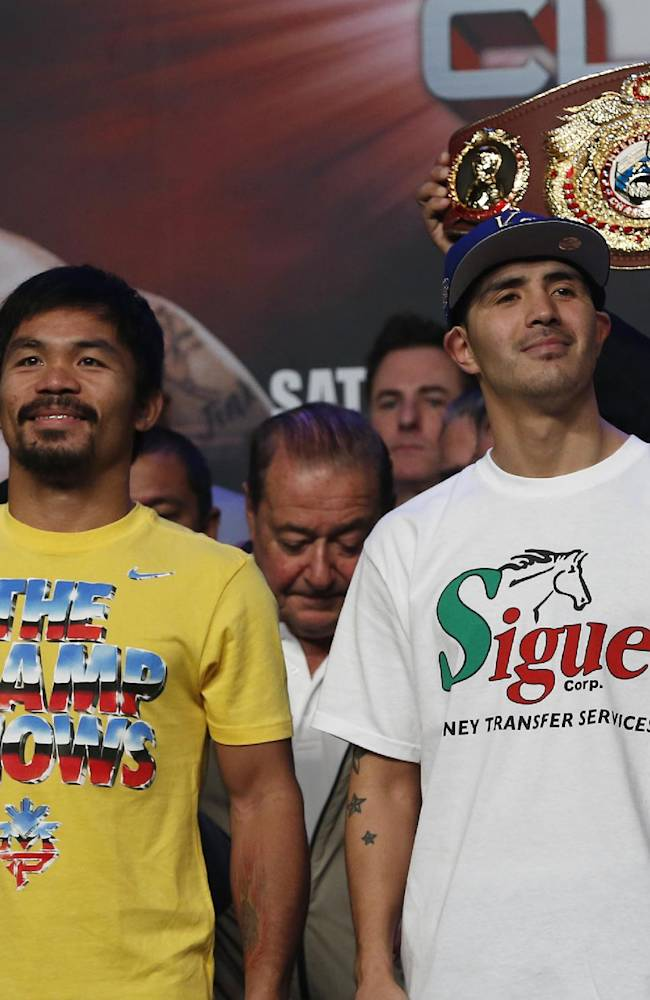 Filipino boxer Manny Pacquiao, left, and Brandon Rios of the United States pose for photos during the weigh-in for their welterweight fight at the Venetian Macao in Macau Saturday, Nov. 23, 2013. Pacquiao and Rios are scheduled to fight in their welterweight boxing match at the casino on Nov. 24