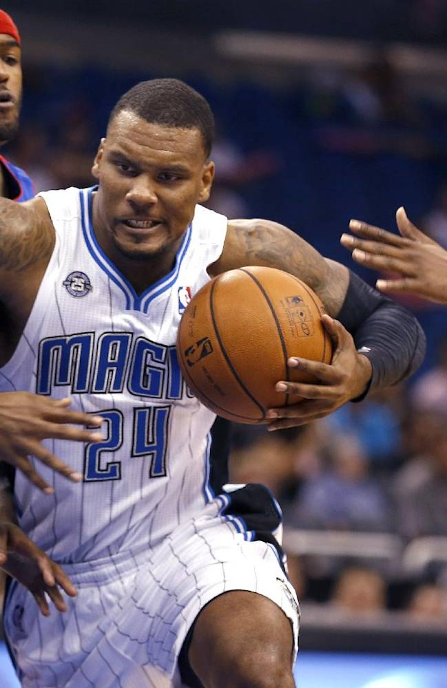Orlando Magic forward Romero Osby (24) drives past Detroit Pistons forward Josh Smith, left, and guard Kentavious Caldwell-Pope (5) during the second half of an NBA basketball game on Sunday,  Oct. 20, 2013, in Orlando, Fla..The Magic won 86-87