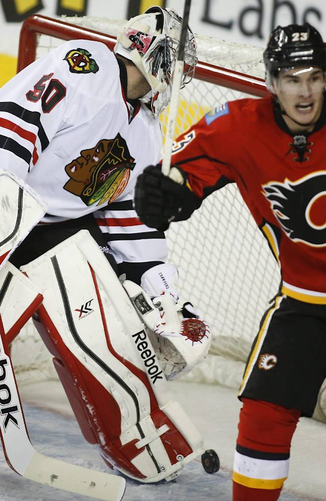 Chicago Blackhawks' goalie Corey Crawford, left, sweeps the puck out of the net as Calgary Flames' Sean Monahan celebrates his team's winning goal during overtime NHL hockey action in Calgary, Alberta, Tuesday, Jan. 28, 2014. The Calgary Flames beat the Chicago Blackhawks 5-4 in overtime