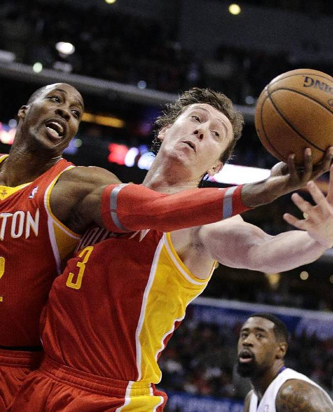 Houston Rockets' Dwight Howard, left, and Omer Asik, of Turkey, reach for a rebound during the first half of an NBA basketball game against the Los Angeles Clippers on Monday, Nov. 4, 2013, in Los Angeles. The Clippers won 137-118