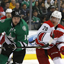 Dallas Stars center Jamie Benn (14) and Carolina Hurricanes center Riley Nash (20) chase the puck during the second period of an NHL hockey game on Thursday, Feb. 27, 2014, in Dallas The Associated Press