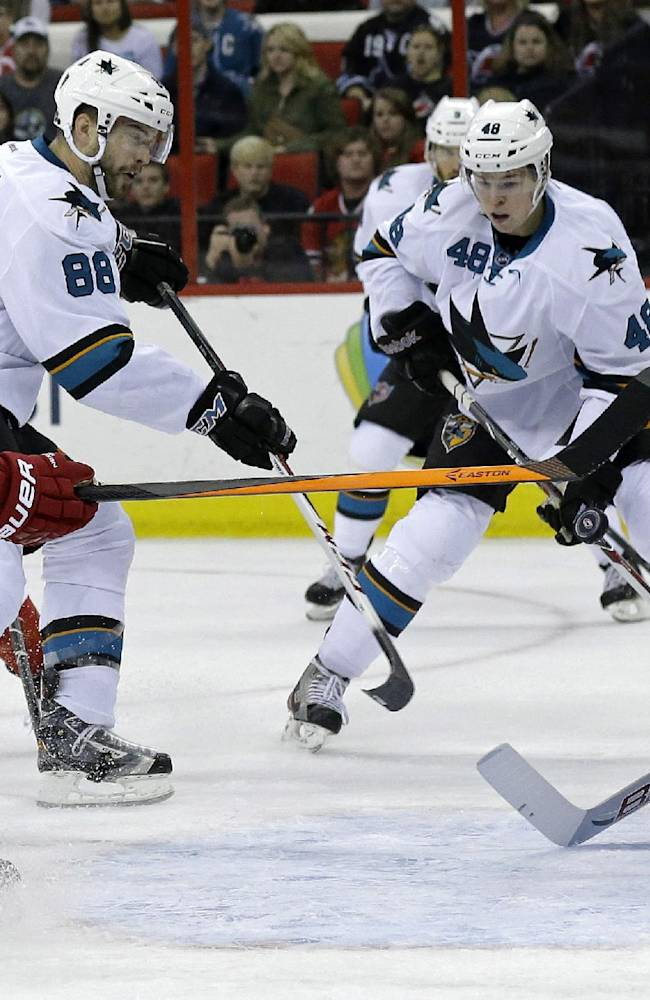 Carolina Hurricanes goalie Cam Ward (30) defends against San Jose Sharks' Brent Burns (88) as Sharks' Tomas Hertl (48), of the Czech Republic, and Hurricanes Radek Dvorak (18), of the Czech Republic, look on during the first period of an NHL hockey game in Raleigh, N.C., Friday, Dec. 6, 2013