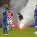 A firefighter removes a flare from the field of play during the Euro 2016 qualifying soccer match between Italy and Croatia, at the San Siro stadium in Milan, Italy, Sunday, Nov. 16, 2014 The Associated Press
