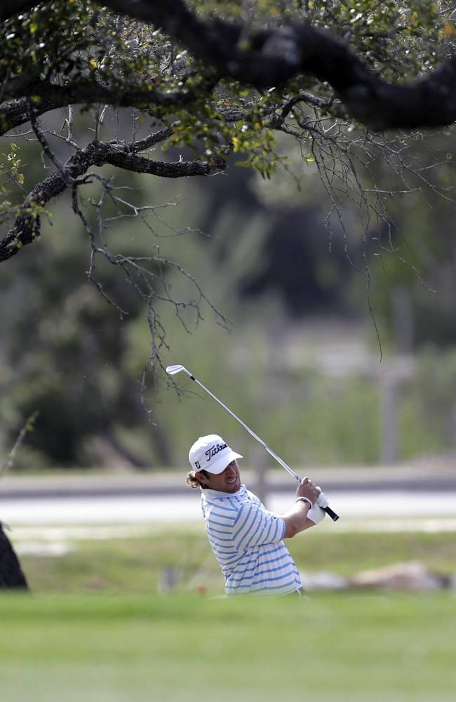 Andrew Loupe hits from the rough on the 18th hole during the third round of the Texas Open golf tournament, Saturday, March 29, 2014, in San Antonio. Loupe is tied for second place after three rounds
