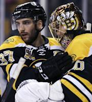 Boston Bruins center Patrice Bergeron (37) congratulates goalie Tuukka Rask after the Bruins defeated the Chicago Blackhawks in an NHL hockey game, Thursday, March 27, 2014, in Boston. Bergeron had two goals and Rask a shutout in the Bruins' 3-0 win. (AP Photo/Charles Krupa)