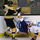 Boston Bruins left wing Milan Lucic (17) drops New York Islanders defenseman Johnny Boychuk, his former teammate, during the first period of an NHL hockey game in Boston, Thursday Oct. 23, 2014. Boychuk played the past six seasons with the Bruins The Asso