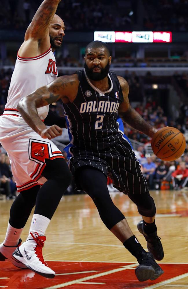Orlando Magic forward Kyle O'Quinn (2) is guarded by Chicago Bulls forward Carlos Boozer during the first half of an NBA basketball game Monday, April 14, 2014, in Chicago. The Bulls won the game 108-95