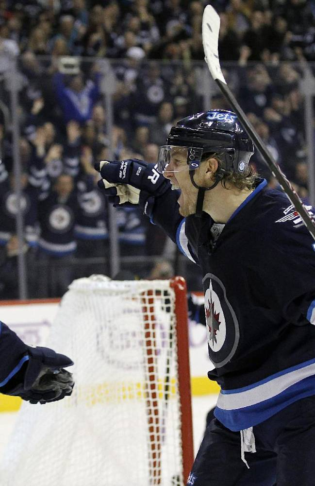 Winnipeg Jets' Andrew Ladd, left,and Bryan Little (18) celebrate after Little scored past Washington Capitals' goaltender Braden Holtby (70) during the second period of an NHL hockey game in Winnipeg, Manitoba, Tuesday, Oct. 22, 2013