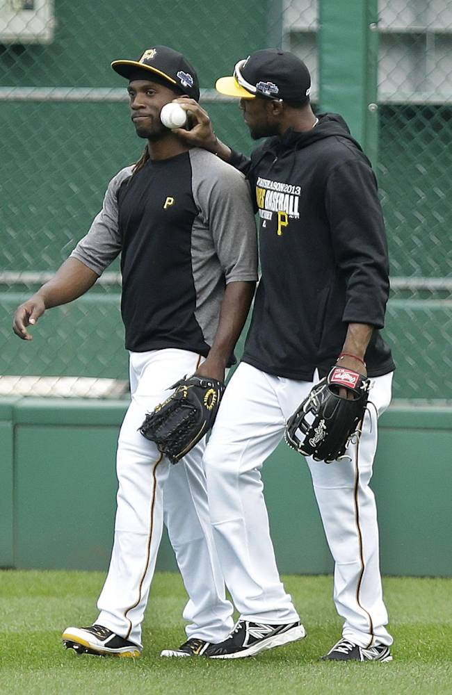 Pittsburgh Pirates' Starling Marte, right, jokes around with teammate Andrew McCutchen after McCutchen was hit in the face by a batting practice line drive by Pirates' Jordy Mercer during the baseball team's workout in Pittsburgh on Monday, Sept. 30, 2013. McCutchen walked off the field and did not return to the workout.  The Pirates are scheduled to face the Cincinnati Reds in the National League Wild Card game Tuesday in Pittsburgh