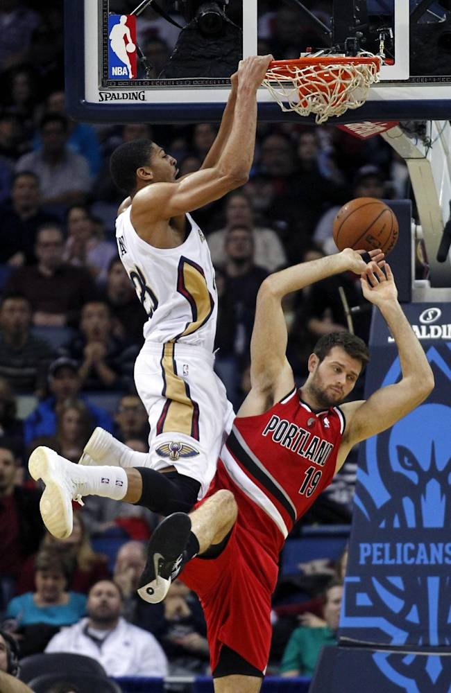 New Orleans Pelicans forward Anthony Davis (23) slam dunks over Portland Trail Blazers center Joel Freeland (19) in the first half of an NBA basketball game in New Orleans, Monday, Dec. 30, 2013