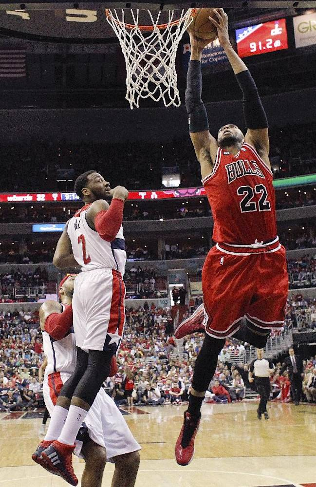 Chicago Bulls forward Taj Gibson (22) shoots for two points as Washington Wizards guard John Wall (2) looks on during the first half of Game 4 of an opening-round NBA basketball playoff series in Washington, Sunday, April 27, 2014