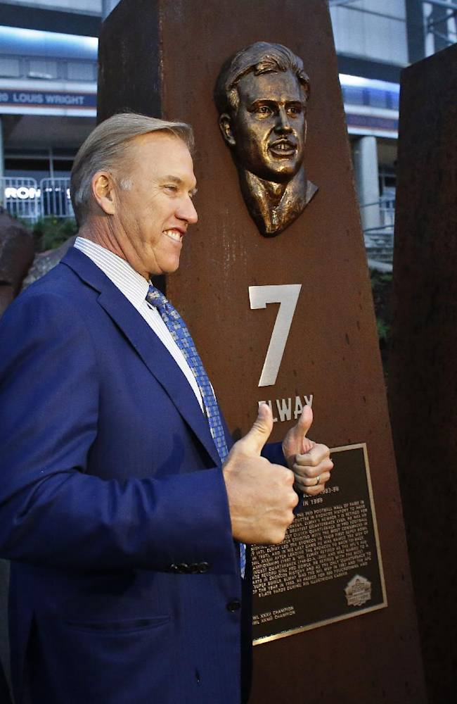 Former Denver Broncos quarterback and current team vice president John Elway gives a thumbs-up as he stands next to a pillar bearing a bronze likeness of Elway from his playing days, at the unveiling ceremony for the Broncos Ring of Fame Plaza at Mile High Stadium on Friday Sept. 27, 2013, in Denver