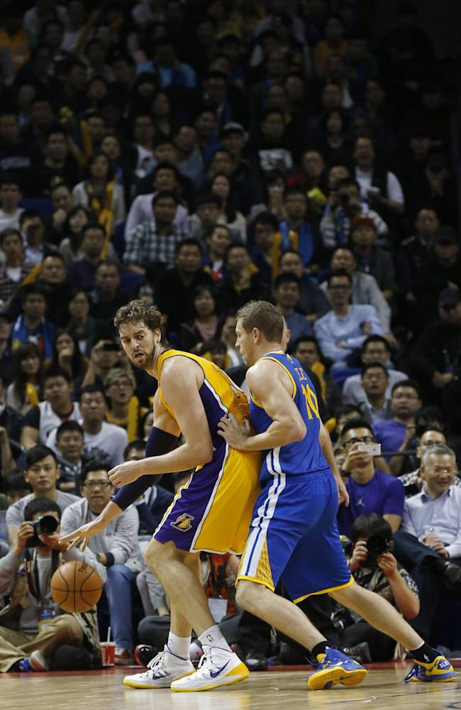 Pau Gasol of Los Angeles Lakers, left, dives against David Lee of Golden State Warriors, right, during a 2013-2014 NBA preseason game between Lakers and Warriors at Mercedes-Benz Arena in  Shanghai, China, Friday, Oct. 18, 2013