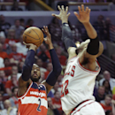 Washington Wizards guard John Wall, left, shoots over Chicago Bulls forward Taj Gibson during the first half in Game 1 of an opening-round NBA basketball playoff series in Chicago, Sunday, April 20, 2014 The Associated Press