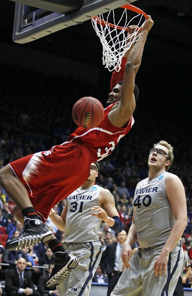 North Carolina State forward Kyle Washington dunks past Xavier center Matt Stainbrook (40) during the first half of a first-round game of the NCAA college basketball tournament, Tuesday, March 18, 2014, in Dayton, Ohio