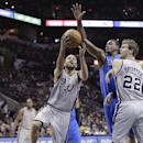 San Antonio Spurs' Tony Parker (9), of France, shoots around Dallas Mavericks' Samuel Dalembert, center, during the first half of an NBA basketball game, Sunday, March 2, 2014, in San Antonio The Associated Press