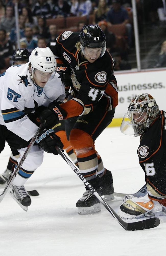 San Jose Sharks' Tommy Wingels, left, and Anaheim Ducks' Hampus Lindholm, of Sweden, scramble for the puck in front of Anaheim Ducks goalie John Gibson during the first period of an NHL hockey game Wednesday, April 9, 2014, in Anaheim, Calif