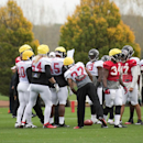 Atlanta Falcons players check a play during a training session at the Arsenal FC training ground in London Colney, England, Wednesday Oct. 22, 2014. The Falcons will play the Detroit Lions in an NFL football game at London's Wembley Stadium on Sunday, Oct