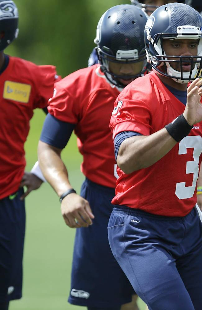 Seattle Seahawks quarterback Russell Wilson (3) catches the ball during a practice drill with backup quarterbacks Keith Price, left, and B.J. Daniels, behind him, at an NFL football organized team activity, Monday, June 9, 2014, in Renton, Wash