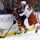 Florida Panthers defenseman Dmitry Kulikov (7) tries to control the puck as Columbus Blue Jackets center Boone Jenner (38) defends in the first period of a hockey game, Saturday, April 12, 2014, in Sunrise, Fla. The Blue Jackets defeated the Panthers 3-2