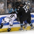 San Jose Sharks center Joe Thornton (19) checks into the boards Los Angeles Kings defenseman Drew Doughty (8) during the second period in Game 3 of their second-round NHL hockey Stanley Cup playoff series, Saturday, May 18, 2013, in San Jose, Calif. (AP Photo/Tony Avelar)