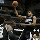 Sacramento Kings' Derrick Williams (13) and Dallas Mavericks' Devin Harris, right, watch as the Kings' Rudy Gay (8) breaks to the basket for a shot in the first half of an NBA basketball game, Saturday, March 29, 2014, in Dallas The Associated Press