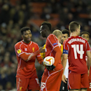 Liverpool's Daniel Sturridge, left, remonstrates with teammate Mario Balotelli, centre, as the latter insists on taking a penalty during the Europa League Round of 32 soccer match between Liverpool and Besiktas at Anfield Stadium in Liverpool, England, Th
