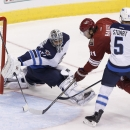 Arizona Coyotes' Martin Hanzal (11), of the Czech Republic, scores a goal against Winnipeg Jets' Ondrej Pavelec, left, of the Czech Republic, as Jets' Mark Stuart (5) defends during the third period of an NHL hockey game Thursday, Oct. 9, 2014, in Glendal