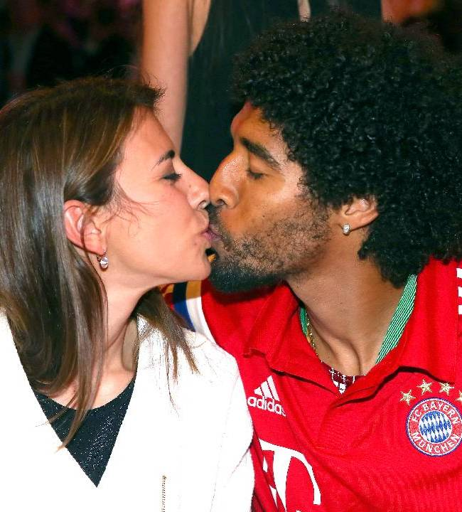 In this picture taken  Saturday May 17, 2014, Bayern Munich's  player Dante kisses his wife Jocelina,  during the after-match party after the club won the German soccer cup final  against Borussia Dortmund in Berlin