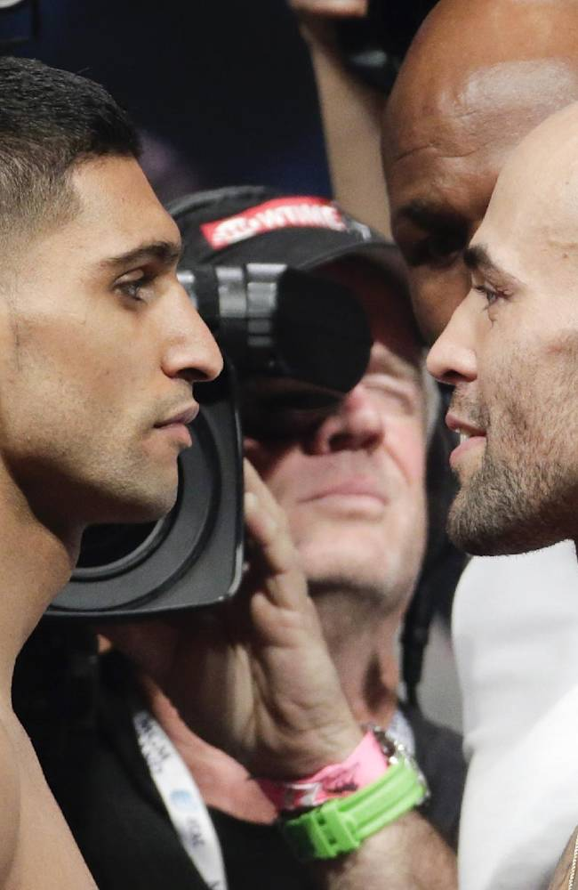 Amir Khan,left, faces Luis Collazo on the scales during the official weigh-in at the MGM Grand Hotel in Las Vegas, Friday, May 2, 2014. Khan is to face Collazo in a 12-round bout for the vacant WBC silver welterweight world title on Saturday