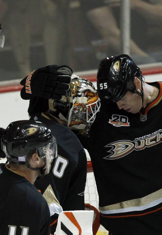 Anaheim Ducks defenseman Bryan Allen, right, congratulates Ducks goalie Viktor Fasth, of Sweden, after defeating the Calgary Flames 3-2 in an NHL hockey game, Wednesday, Oct. 16, 2013, in Anaheim, Calif. Ducks centers Nick Bonino (13) and Saku Koivu (11), of Finland,  skate around the net