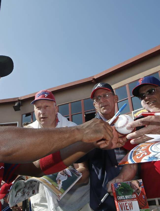 Philadelphia Phillies shortstop Jimmy Rollins, left, autographs a baseball for fans before a spring exhibition baseball game against the Atlanta Braves in Clearwater, Fla., Monday, March 10, 2014
