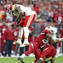 Kansas City Chiefs wide receiver Dwayne Bowe, left, leaps over Arizona Cardinals free safety Rashad Johnson, right, and Justin Bethel, center, during the first half of an NFL football game, Sunday, Dec. 7, 2014, in Glendale, Ariz The Associated Press