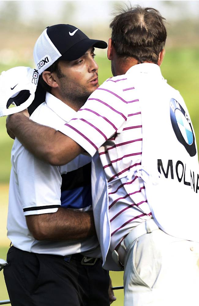 Francesco Molinari of Italy, left, and his caddie embrace after finishing the 18th hole during the final round of the BMW Masters golf tournament at the Lake Malaren Golf Club in Shanghai, China, Sunday, Oct. 27, 2013