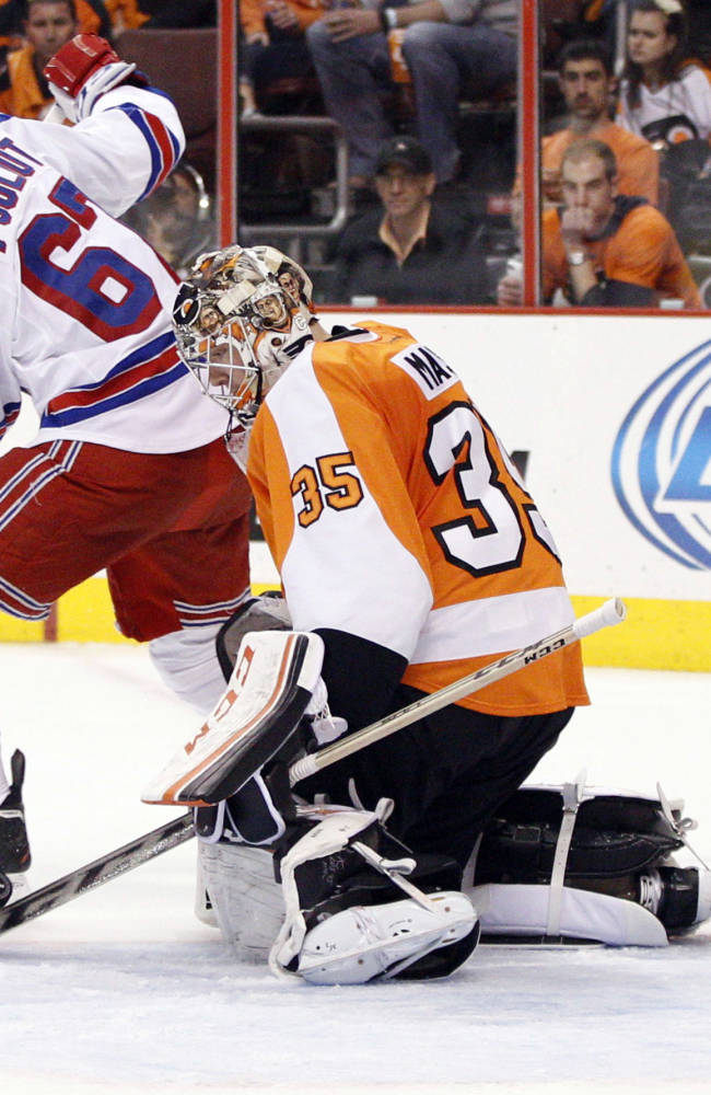 Philadelphia Flyers' Steve Mason, right, stops the puck with his stick as New York Rangers' Benoit Pouliot, left, looks back for it during the second period in Game 4 of an NHL hockey first-round playoff series on Friday, April 25, 2014, in Philadelphia