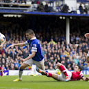 Everton's Kevin Mirallas, centre left, scores against Arsenal despite the attentions of Mikel Arteta, bottom right, during their English Premier League soccer match at Goodison Park Stadium, Liverpool, England, Sunday April 6, 2014
